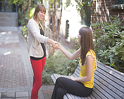 two girls shaking hands and connecting in person